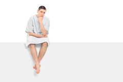 Worried male patient sitting on a blank panel. Isolated on white background Royalty Free Stock Photography