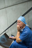 Worried male surgeon holding x-ray on staircase. In hospital Stock Photography