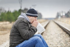 Worried man breathe into a paper bag. On a railway Royalty Free Stock Photos