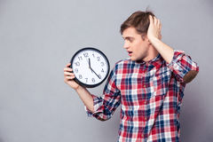 Worried man in checkered shirt holding and looking at clock Royalty Free Stock Photos