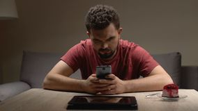 Worried man checking nervously smartphone and tablet, problem thoughts, despair