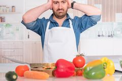 Worried man before cooking at home for dinner royalty free stock image