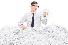 Worried man covered in shredded paper Royalty Free Stock Photography