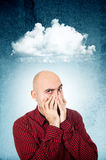 Worried man covering face. Worried young adult bald man covering face with his hands, cloud of thoughts above his head Stock Photo