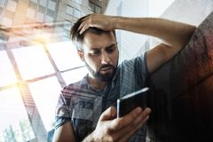 Worried man discovering unpleasant news when reading messages. Unexpected news. Emotional tired young man feeling worried and sitting on the sofa with his hand Stock Photography