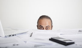 Worried man face looking behind table of office Royalty Free Stock Photography