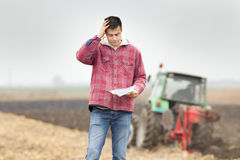 Worried man on the field. Worried young farmer standing on field and looking at papers from bank, tractor in background stock photo