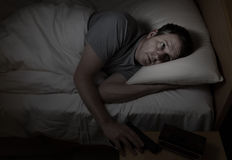 Worried man grabs gun from night stand while in bed Royalty Free Stock Image