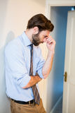 Worried man with hand on forehead leaning on wall Stock Image