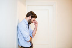 Worried man with hand on forehead leaning on wall Royalty Free Stock Photo