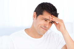 Worried man having a headache in his bedroom Stock Photos