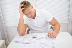 Worried man looking at bills Stock Photography