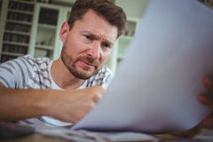 Worried man looking at his bills. At home royalty free stock photo