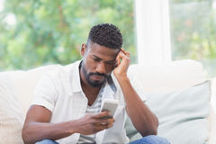 Worried man looking at his phone. At home in the living room Stock Photo
