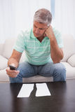 Worried man looking at ripped page sending a text Stock Image