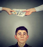 Worried man looking up at hands exchanging money. Worried man looking up at two hands exchanging money Royalty Free Stock Image