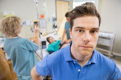 Worried Man With Nurses Examining Pregnant Woman Stock Photography