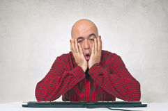 Worried man at office table. Worried young adult bald man sitting at the office table in front of the computer keyboard Royalty Free Stock Photography