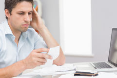 Worried man paying his bills online with laptop at home Stock Image