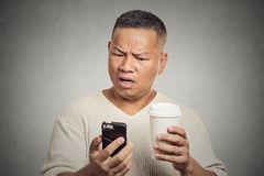 Worried man reading bad news on smart phone drinking cup of coffee Stock Image