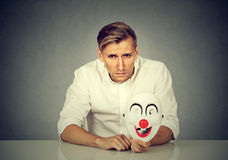 Worried man with sad expression holding clown mask expressing cheerfulness Royalty Free Stock Photo