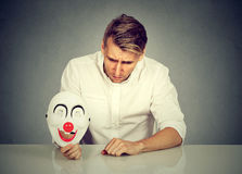 Worried man with sad expression holding clown mask expressing cheerfulness. Portrait young upset worried man with sad expression holding clown mask expressing stock photography