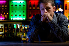 Worried man sitting at bar with whiskey glass. Dar Royalty Free Stock Photos
