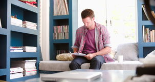 Worried Man Sitting On Couch In Home Office Reading Document. Worried man sitting on couch in home office and reading document before checking information on stock video