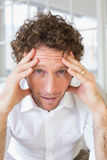 Worried man sitting with head in hands at home Royalty Free Stock Images