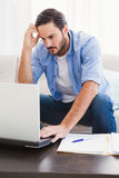 Worried man sitting at table using laptop to pay his bills Royalty Free Stock Photography