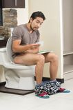 Worried man sitting on the toilet running out of Stock Images