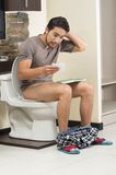 Worried man sitting on the toilet running out of Royalty Free Stock Photography