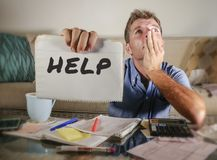Worried man in stress at home calculating month tax expenses with calculator accounting payments sad and depressed asking for help royalty free stock photo