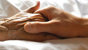 Worried man taking and gently stroking hand of his sick mother showing care or love. Son comforting wrinkled arm of
