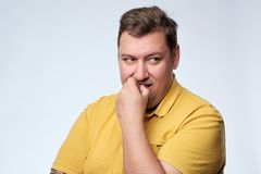 Worried man tries to remember something. Worried fat caucasian man tries to remember something. He is worried and looks with doubt Stock Photo