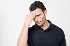 Worried man trying to remember something. Confused young man holding hand to forehead royalty free stock photo