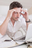 Worried man under pressure. Worried man in office under deadline pressure, working with laptop Stock Images