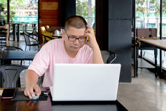 worried man using a laptop computer and looking at the screen., Stock Images