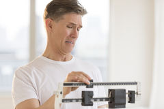 Worried Man Using Weight Scale At Gym Royalty Free Stock Image