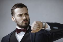 Worried Man with Watch. We have no more . Portrait of the handsome serious bearded young man in trendy suit black vest and white shirt, standing, looking at the stock image
