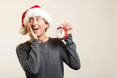 Worried man wearing Santa Claus helper hat. Santa guy holding red clock, isolated on white. Time is coming. New Year and Christmas stock images