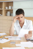 Worried Man Working on Finances. Young man working on his home finances in the kitchen Royalty Free Stock Photos