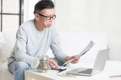 Worried mature Asian man looking at the bills. Royalty Free Stock Photo