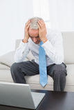 Worried mature businessman with laptop at home Stock Photography