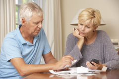Worried Mature Couple Checking Finances And Going Through Bills Together Royalty Free Stock Images