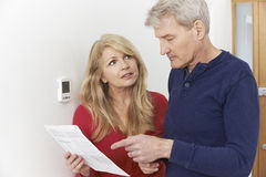Worried Mature Couple With Bill Turning Down Central Heating Stock Image