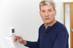 Worried Mature Man With Bill Turning Down Central Heating Thermostat. Worried Man With Bill Turning Down Central Heating Thermostat royalty free stock image