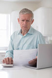 Worried Mature Man With Laptop Calculating Household Finances Stock Photos