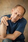 Worried mature man sitting at studio Royalty Free Stock Image