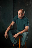 Worried mature man sitting at studio Stock Images